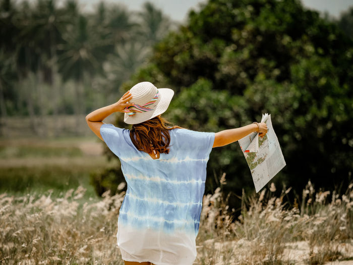 Woman wearing hat while holding map on field against trees