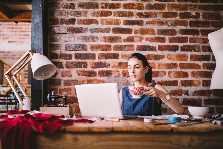 Woman Having Drink While Using Laptop Against Brick Wall