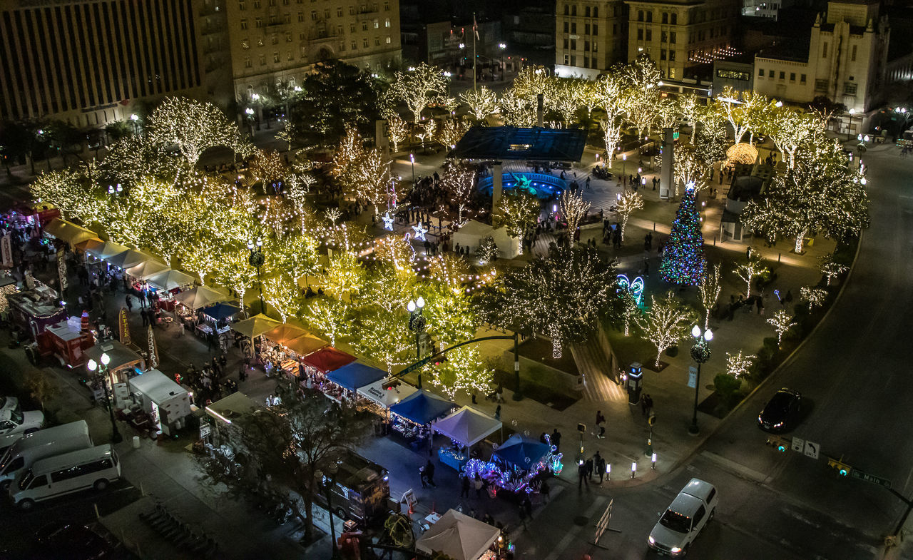 high angle view, illuminated, city, architecture, night, tree, built structure, building exterior, decoration, celebration, crowd, christmas, street, large group of people, group of people, land vehicle, holiday, plant, motor vehicle