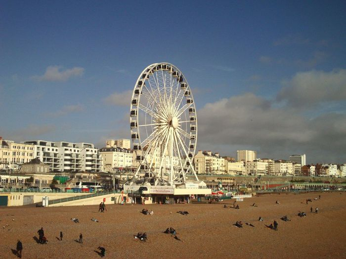 Big Wheel With People On Beach Against Sky