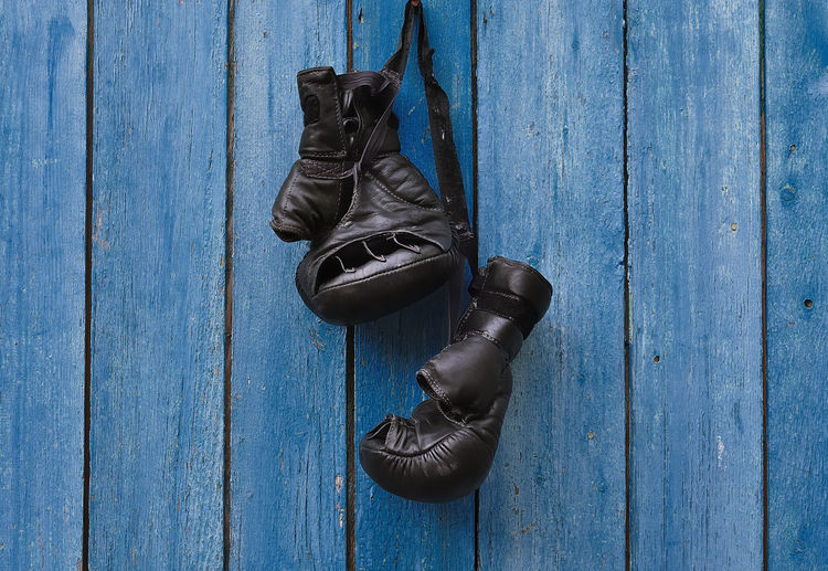 Close-up of black boxing gloves hanging on blue wood