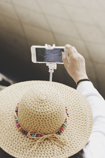High angle view of person wearing hat while taking selfie with mobile phone