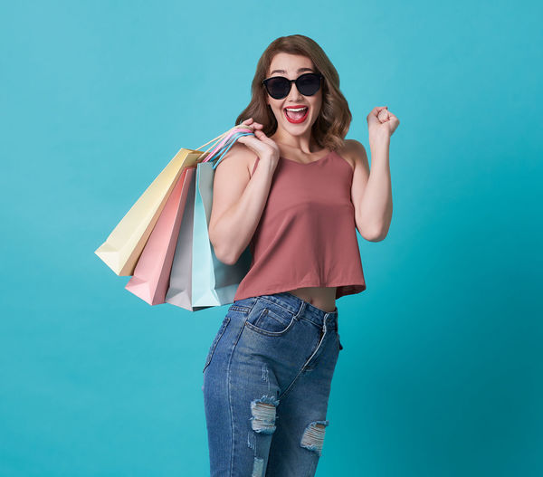 Portrait of happy woman holding shopping bags while standing against turquoise background