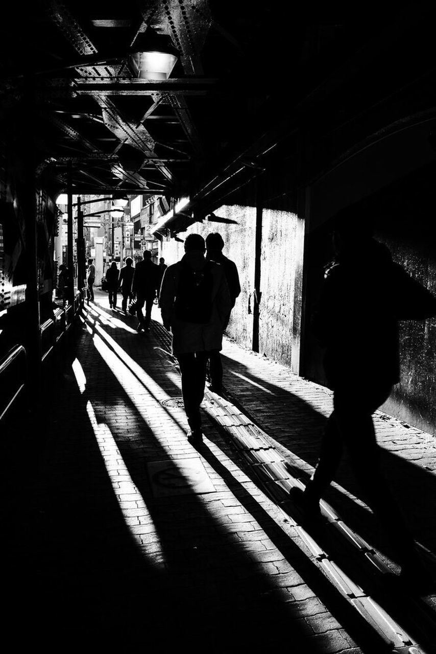 architecture, walking, men, shadow, real people, rear view, transportation, sunlight, group of people, people, lifestyles, full length, built structure, rail transportation, indoors, silhouette, day, leisure activity, nature, railroad station, track, waiting