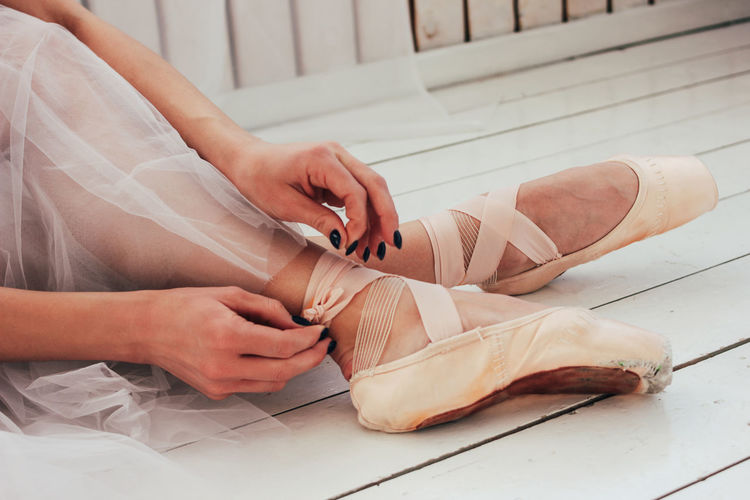Low section of woman wearing ballet shoe while sitting on wooden floor