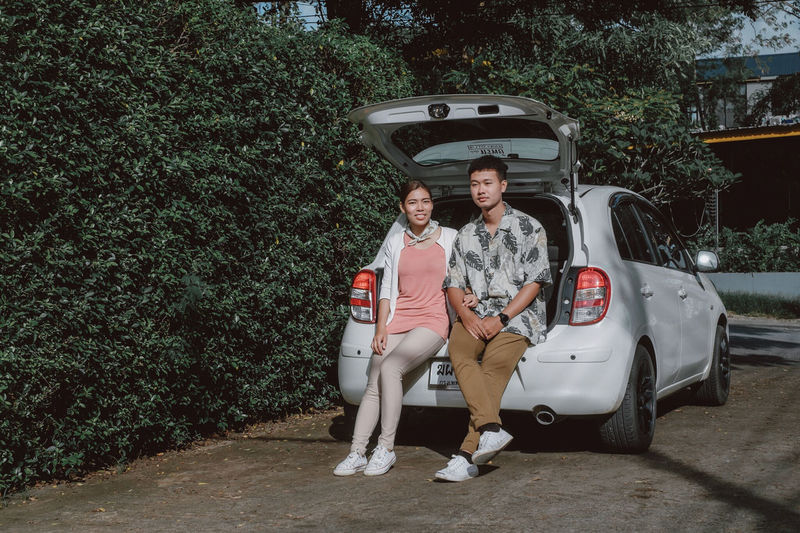 Couple sitting in car trunk