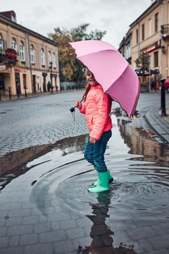 Full length of woman holding umbrella during rainy season