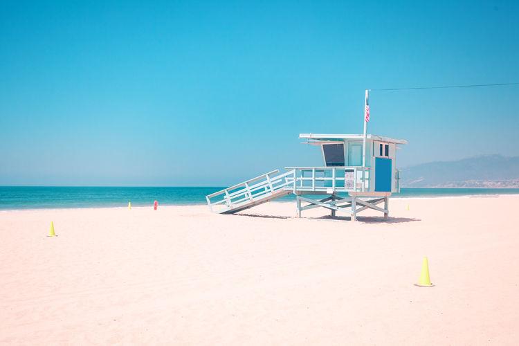 Lifeguard hut on beach against clear blue sky