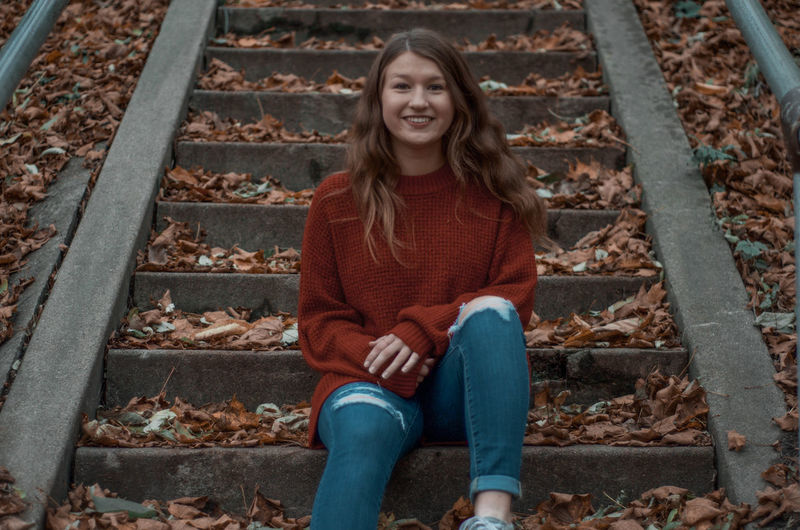 Portrait of a smiling girl sitting on staircase