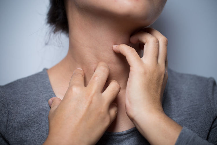 Midsection Of Woman With Neckache Against Gray Background