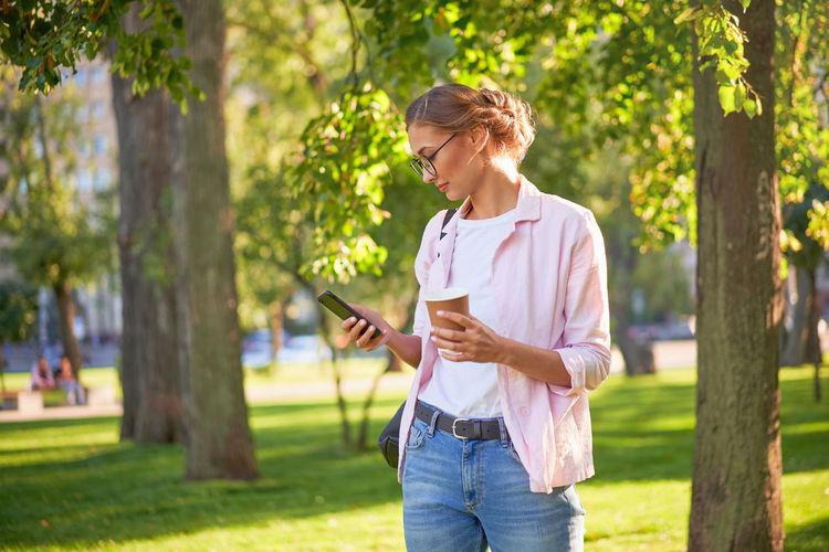 Full length of woman using phone while standing on tree