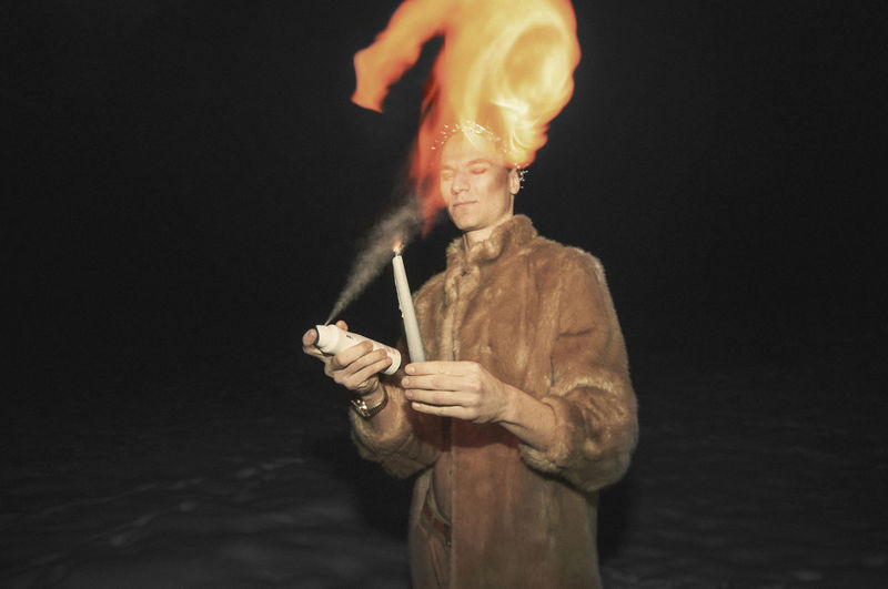 Man blowing perfume on candle while standing on snow at night
