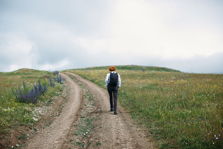 Alone Casual Clothing Cloud Country Road Countryside Day Female Field Girl Grass Hike Hiker Hiking Landscape Lonely Nature Outdoors Path Road Rural Scene Sky Solitude The Way Forward Walking