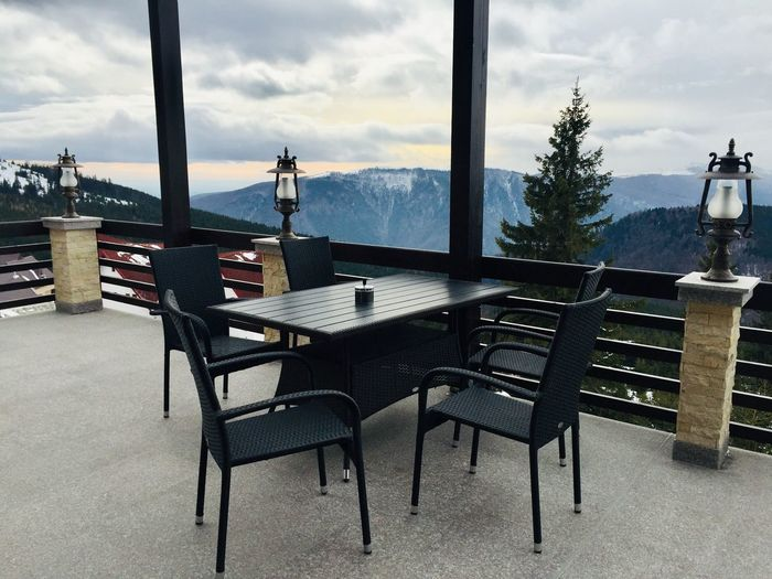 Dining table at a restaurant on the terrace surrounded by mountains and forests Premises Hunger Nobody View Restaurant Scene Idyllic Scenery Landscape Beauty In Nature Nature Coniferous Tree Evergreen Trees Forest Mountains Outdoors Day Terrace Dining Table Restaurant Seat Cloud - Sky Sky Chair Table Absence No People Nature Architecture Scenics - Nature