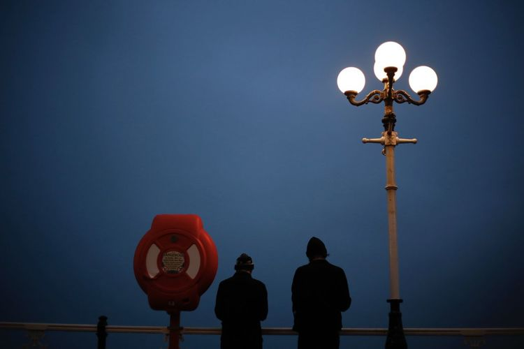 Friends Standing By Street Light Against Clear Sky At Night