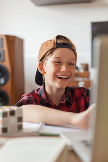 Happy elementary student talking to someone over video call at home.
