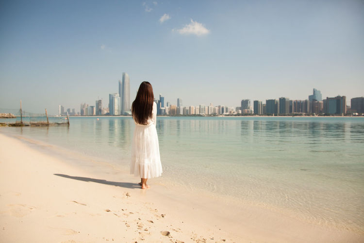 Architecture Beach Beauty In Nature Building Exterior Built Structure City Clear Sky Day Full Length Leisure Activity Nature One Person One Woman Only Outdoors Real People Rear View Sand Sea Sky Skyscraper Travel Destinations Vacations Water Women Young Adult
