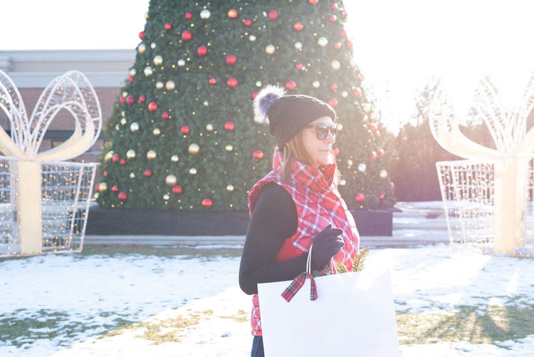 Woman standing by christmas tree during winter