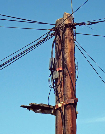 Total mess on telecommunication pylon IT Cable Communication Complexity Day Electrical Equipment Internet Low Angle View No People Power Line  Technology Telephone Line Telephone Pole Wires