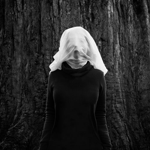 Woman with face covered standing against tree trunk