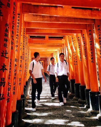 Full length of people walking on orange wall