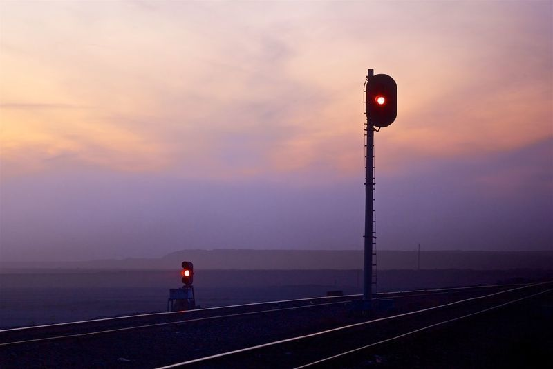 Signal by railroad tracks against sky at sunset