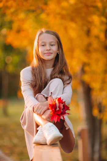 Portrait of a beautiful young woman holding red flower