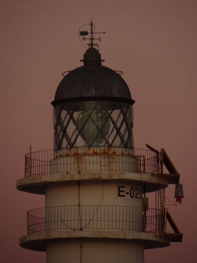 Lighthouse by building against sky during sunset