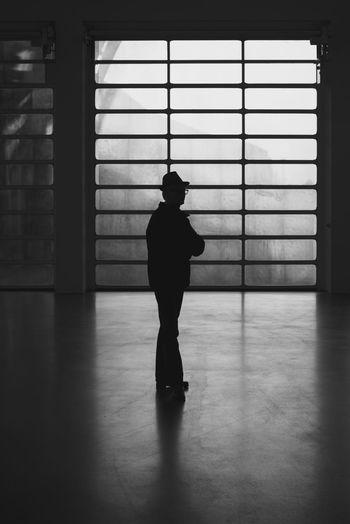 Man Standing Against Window