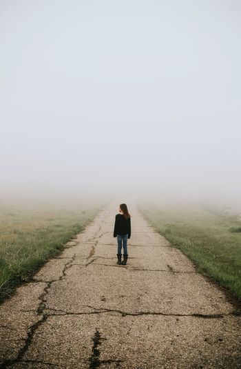 Rear view of girl standing on road during foggy weather