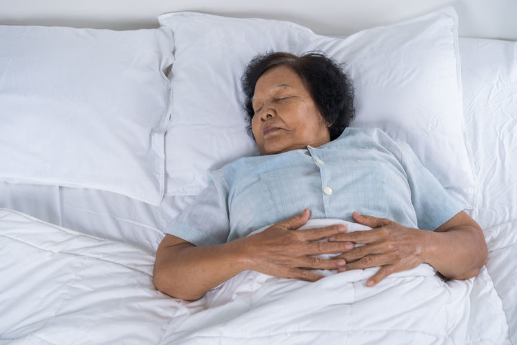 High Angle View Of Senior Woman Sleeping On Bed At Home