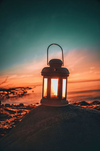 Close-Up Of Old-Fashioned Lantern On Rock At Beach Against Sky During Sunset