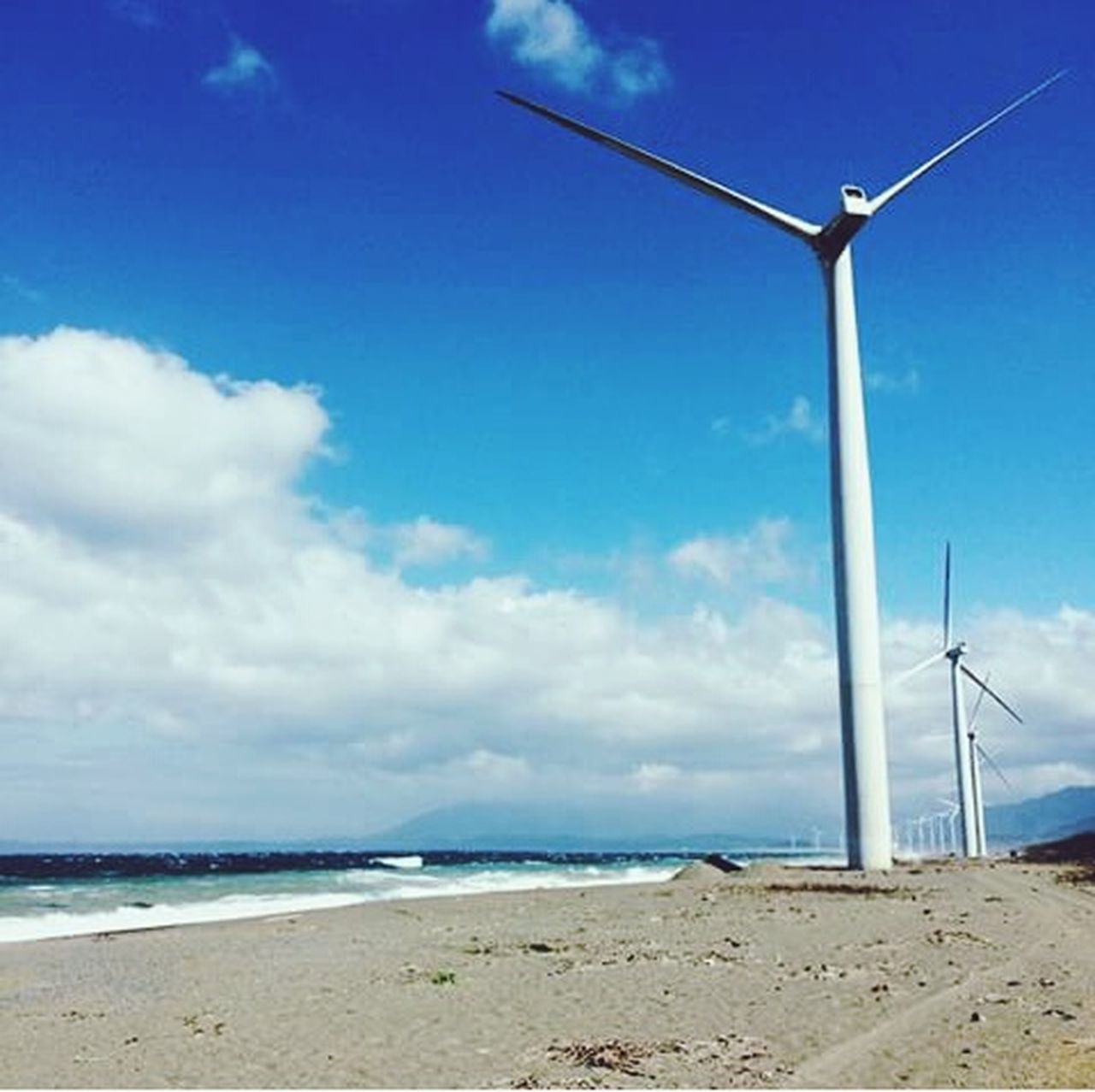 cloud - sky, wind power, sky, sea, environmental conservation, wind turbine, beach, alternative energy, nature, fuel and power generation, blue, wind, sand, outdoors, horizon over water, no people, scenics, day, rural scene, water, power in nature, technology