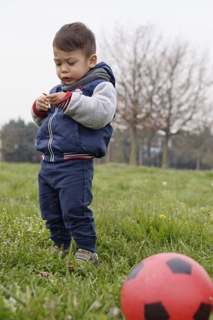 Childhood Grass Full Length One Person Child One Boy Only Males  Boys Leisure Activity Children Only Day Outdoors Real People Playing Portrait People Nature Soccer Player Human Body Part Football
