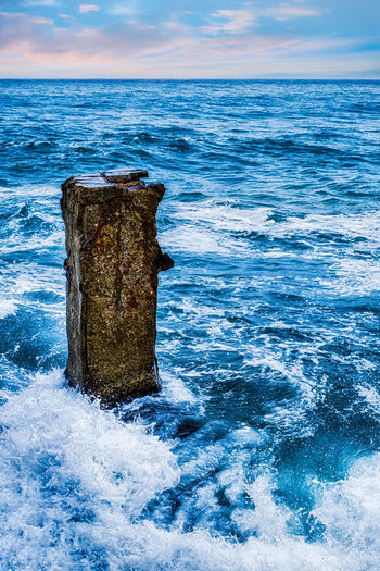 Sea waves hitting the old concrete pillar Sea Waves Hitting The Old Concrete Pillar Sea Water Concrete Structure Old Blue Ocean Sea Water Horizon Horizon Over Water Beauty In Nature Scenics - Nature Sky Nature No People Land Tranquility Tranquil Scene Day Outdoors Motion Blue Wave Cloud - Sky Remote
