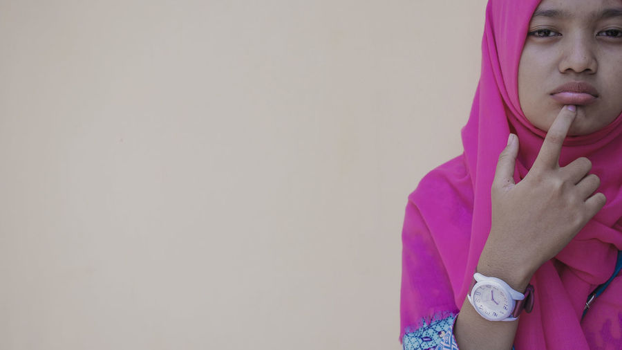 Portrait of young woman wearing pink hijab standing against beige background