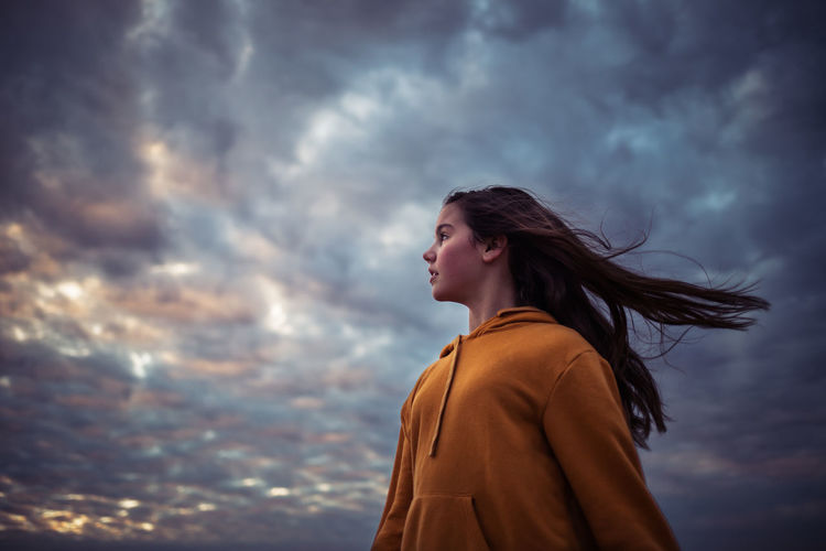Low angle view of girl with long hair looking away while standing against cloudy sky