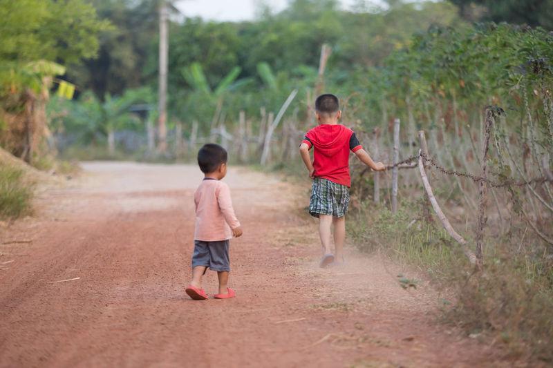 Rear view of boys walking on dirt road