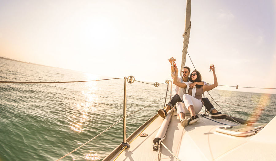 Young lovers couple on sail boat with champagne at sunset - Exclusive luxury concept with rich millennial people lifestyle on tour around the world - Soft backlight focus on warm sunshine filter Couple Love Luxury Travel Sailboat Sailing Boat Sailing Ship Boat Sailing Anniversary Rich Lifestyle People Yacht Sail Young Happy Summer World Trip Wanderlust Wine Champagne Celebrating Fancy