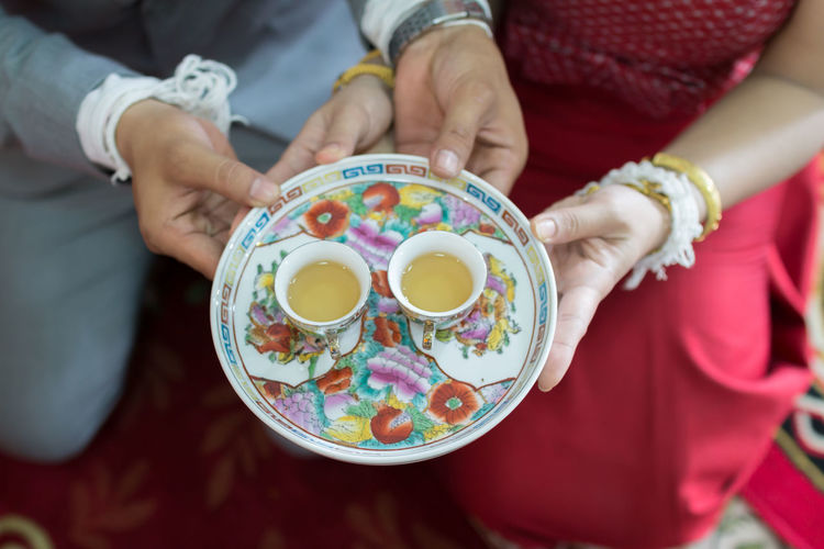 Midsection of bride and groom holding tea on tray