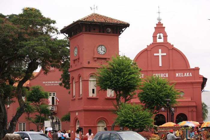 A Stadthuys building in Melaka, Malaysia standing proudly to welcome tourist Historical Building Historycal Place Architecture Bell Tower Building Exterior Built Structure Clock Clock Tower Day Historic History Large Group Of People Men Outdoors People Place Of Worship Portugese Portugese Settlement Real People Religion Sky Spirituality Time Tower Tree
