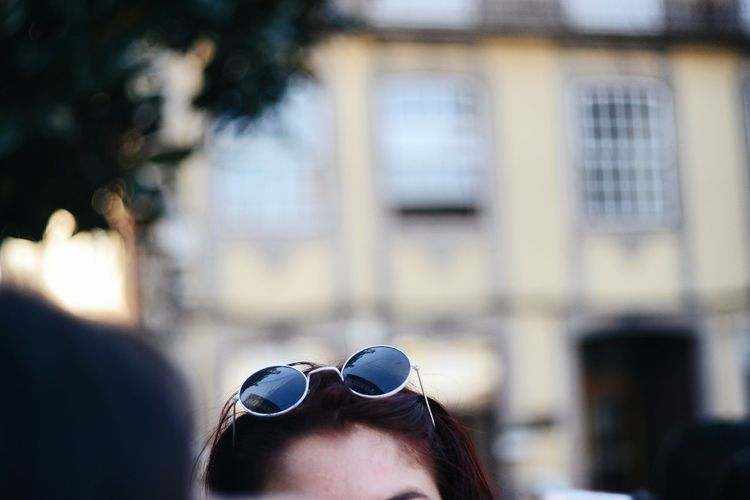 Cropped image of woman head wearing sunglasses against building outdoors