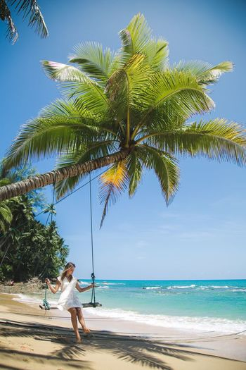 Woman Sitting On Swing At Beach Against Blue Sky