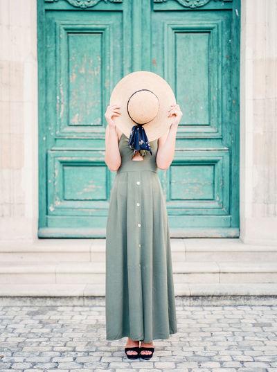 Woman with hat standing against door