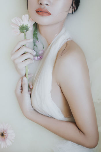 Midsection of woman holding flower against white background