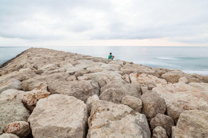 Man sitting on jetty over sea against sky