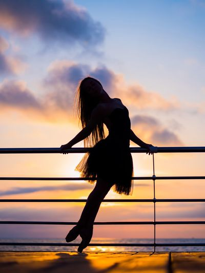 Silhouette Mid Adult Woman Standing By Railing Against Sky During Sunset