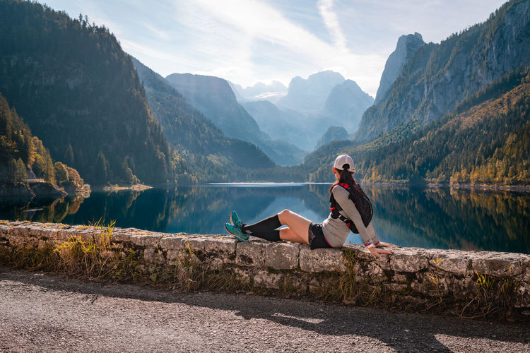 Woman sitting by lake against mountains