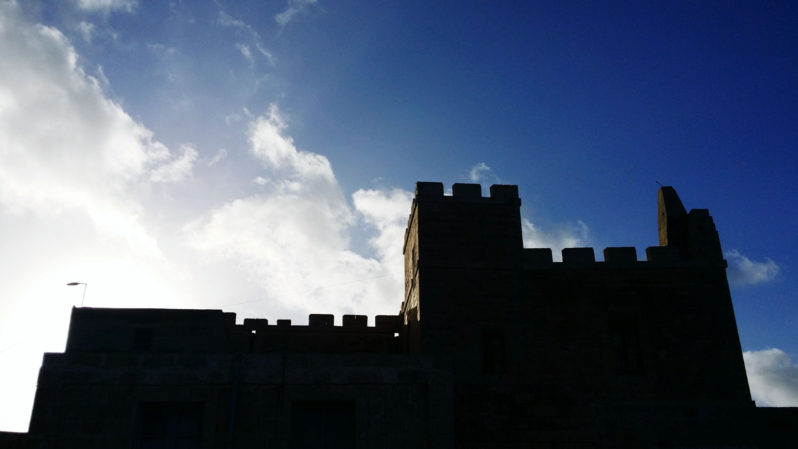 architecture, building exterior, built structure, low angle view, sky, blue, city, building, silhouette, cloud, cloud - sky, outdoors, copy space, no people, day, tower, dusk, high section, sunlight, tall - high