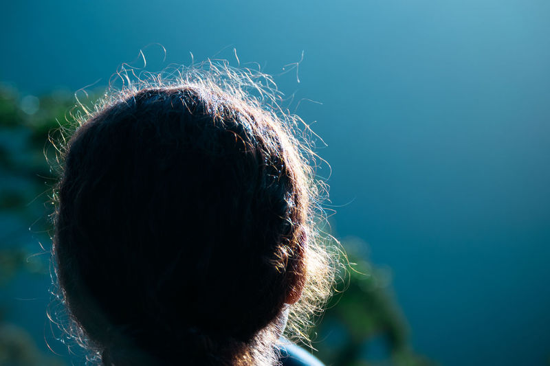 Close-up rear view of woman standing outdoors